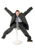 Boy in man's suit sitting on chair and smiling Royalty Free Stock Photography