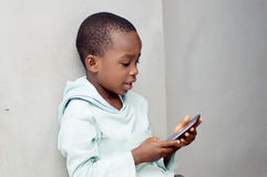 Boy manipulating a mobile phone. This little boy sitting against the wall  manipulates a mobile phone with emotion Royalty Free Stock Photo