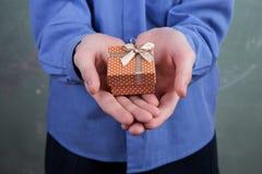 Boy& x27; mano de s que sostiene la pequeña caja de regalo con los lunares Foto de archivo