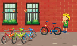 Boy and many bikes by the building Royalty Free Stock Image