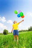 Boy with many colorful balloons in green field Stock Images