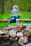 Boy with map sitting near a campfire. Royalty Free Stock Images