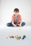 Boy Marble Play. A boy plays a game of marbles. Vertical, isolated studio portrait stock photography