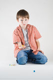 Boy Marble Play. A boy holds out a yellow marble in his hand, while kneeling beside a pile of marbles. Vertical, isolated studio portrait royalty free stock photo