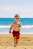 Boy Marching on Sandy Beach Away from Ocean. A happy boy marches away from the ocean with a cracker in his hand. Sand kicks off of his foot as he walks Stock Image