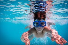 Boy in mask dive in swimming pool. Underwater shoot stock image