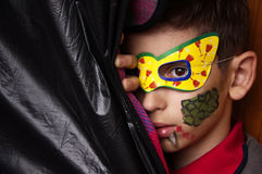 The boy in the mask. Peeked out from behind the black curtain Stock Photos