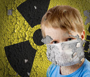 Boy in mask over old Sign of radiation Stock Images