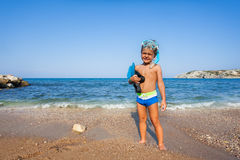 Boy with mask and paddles stands on the seashore Royalty Free Stock Photography