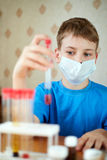 Boy in mask-respirator sits at table with chemical reagents. And looks at a test tube, which he holds in his hand stock images