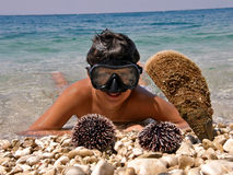 Boy with mask, urchin andcrustacean. Portrait of a smiling  teenage boy with a diver mask, lying in shallow waters of the Adriatic Sea (Croatia - Dalmatia) with Royalty Free Stock Photos