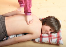 Boy massaged by a girl Stock Photos
