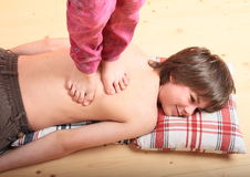 Boy massaged by a girl. Little boy - kid with naked back lying on pillows on wooden floor being massaged with bare feet of little girl Royalty Free Stock Photos