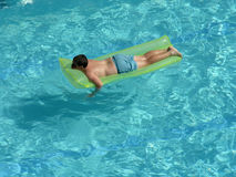 Boy on mattress in pool. Boy swimming on mattress in pool royalty free stock photography