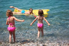 Boy on mattress in sea and girls nearby Royalty Free Stock Photos
