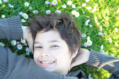 Boy on meadow with daisies. Happy boy on meadow with daisies Royalty Free Stock Photo