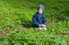 Boy in the meadow. Four year old boy in the meadow. He is squatting in the lush grass. Boy hold toy gun. He is dressed in windbreaker and sweatpants Stock Photos