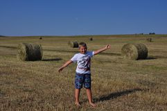 Boy in the meadow near haystack Stock Photography