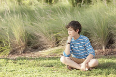 Boy in the meadows. Handsome young boy sitting in the meadows stock photos