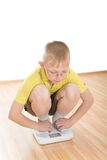 Boy measures weight on floor scales Royalty Free Stock Photos