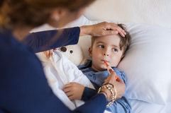 Boy measuring fever. Sick boy with thermometer laying in bed and mother hand taking temperature. Mother checking temperature of her sick son who has thermometer Stock Image