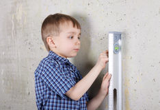 Boy measuring vertical of wall by level Royalty Free Stock Images
