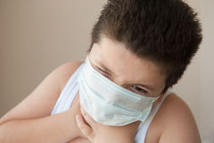 Boy in the medical mask keeps for a sick throat Royalty Free Stock Image
