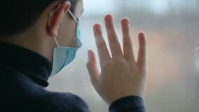 Boy in medical mask slams his hand against window out of boredom during world coronavirus epidemic