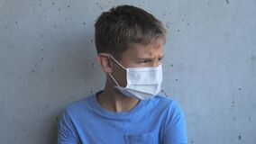 Boy with medical protective mask looking at camera and turns his head to the side. Kid standing near grunge gray wall