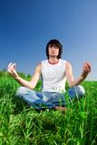 Boy is meditating on grass Royalty Free Stock Images