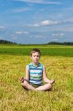 Boy meditating on the green field Stock Photo