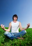Boy is meditating on green grass Stock Photos