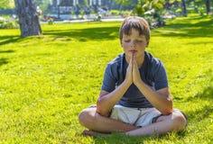 Boy meditating outdoors Stock Photo