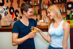 Boy meets a girl and treat her cocktail in the bar. Horizontal photo Royalty Free Stock Photos