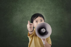 Boy and megaphone in front of blank board. In class Royalty Free Stock Image
