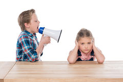 Boy with megaphone yelling on his sad sister isolated on white Stock Image