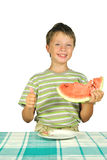 The boy with melon at the table Royalty Free Stock Images