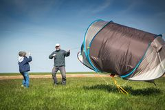 A boy and a man in a vast field with a tent. Strong wind, tent flies. Adventure in the campaign. A boy and a men in a vast field with a tent. Tent blows the wind stock images
