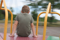 Boy On Merry Go Round. Medium view of boy sitting on spinning merry-go-round while park background blurs by. Horizontal format Stock Image