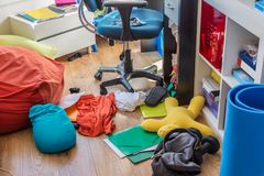 Boy messy bedroom with clothes and pillows on the floor. Boy messy bedroom with clothes and colorful pillows on the floor Royalty Free Stock Image