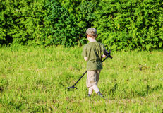 Boy with a metal detector on a green meadow Royalty Free Stock Photos