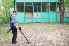 Boy with a metal detector. Boy is looking for valuables with a metal detector Royalty Free Stock Photos
