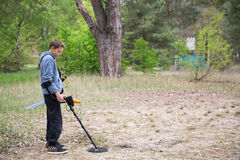 Boy with a metal detector. Boy is looking for valuables with a metal detector Stock Photography
