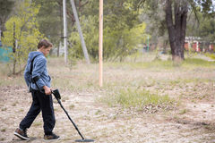 Boy with a metal detector. Boy is looking for valuables with a metal detector royalty free stock photography