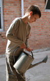 Boy with metal watering-pot against brickwall Stock Photos