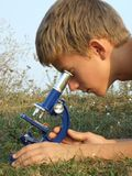 Boy and microscope Stock Image