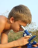 Boy and microscope Royalty Free Stock Photography