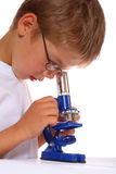 The boy with a microscope. On white Stock Images