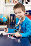 Boy with microscope at home Stock Images