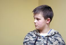Boy in military blouse. A boy (teenager) wearing a camouflage blouse. He looks focused, concerned, a bit angry, not joyful Stock Photos